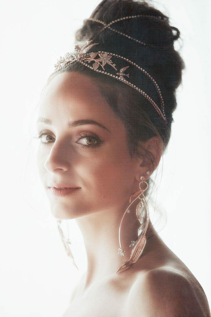 retrato de novia mirando a camara peinada con corona y pendientes largos con cuello desnudo y con fondo blanco