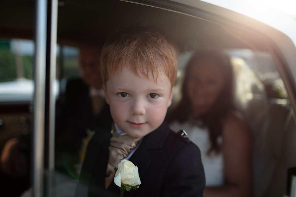 retrato fotografico de un nino mirando a la camara en el coche de los recien casados en ibiza