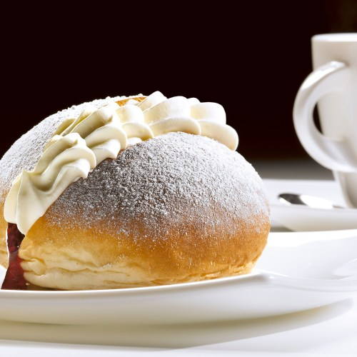 Devonshire split cream donut with jam and white cup and saucer in background - Food and drink photography