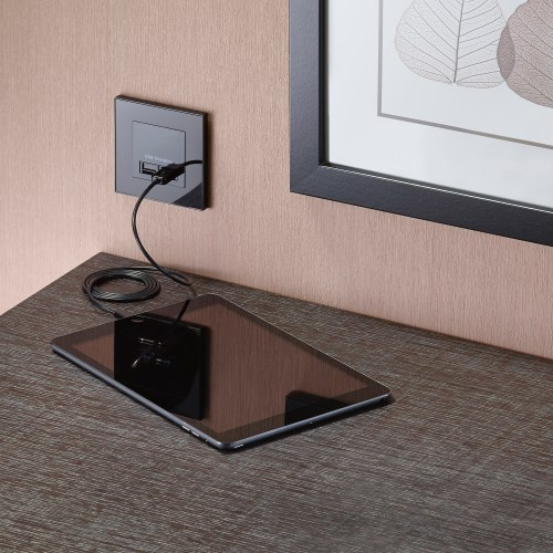 ipad charging in MK Black gloss Dimensions socket on dark wood table with picture frame hanging on wall electrical photography