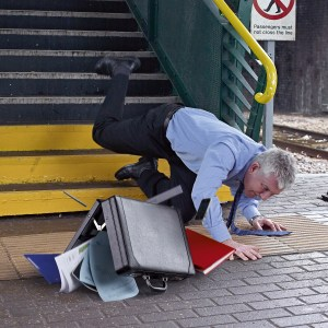 Older grey haired professional man wearing shirt trousers & tie tripping down train station steps and contents of briefase spilling onto platform - People photography
