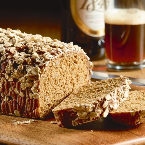 Cut loaf of Sunflower oat and ale loaf on wooden board with glass of ale in background - Food and drink photography