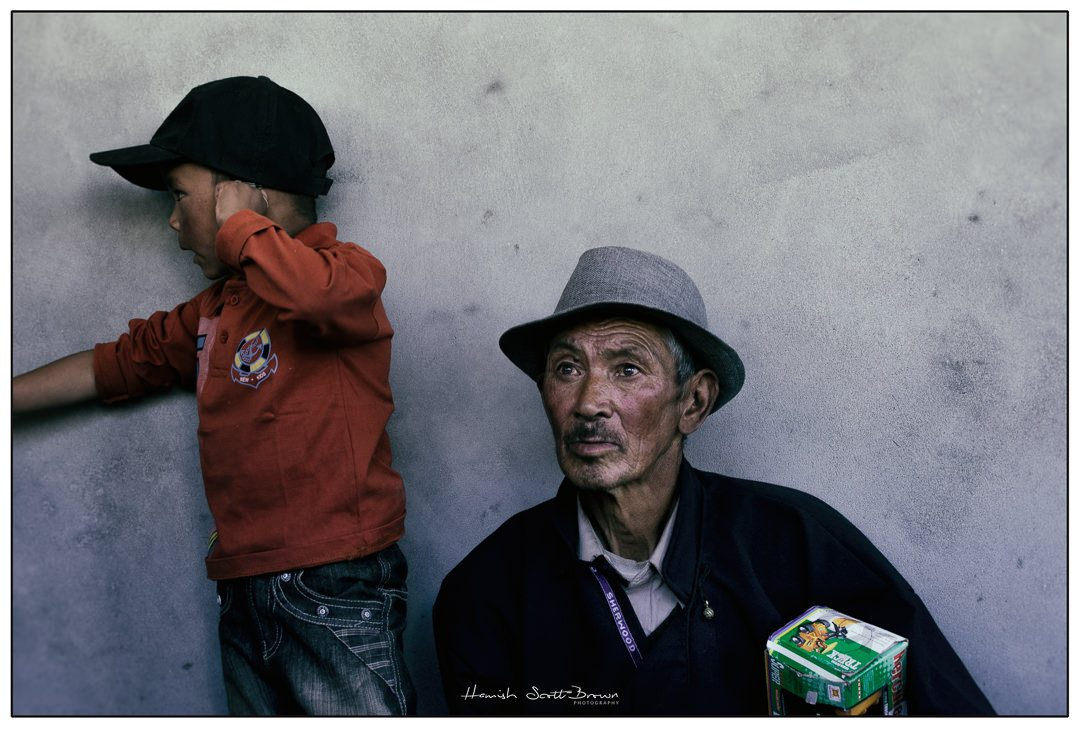 young boy with his grandfather at a buddhist festival near Leh