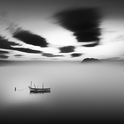 Storm clouds moving quickly across the sky. A rowboat sits alone in the waters below. Long exposure, black and white.