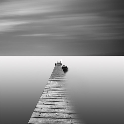 Sunken pier extends out towards the horizon - black and white, long exposure.