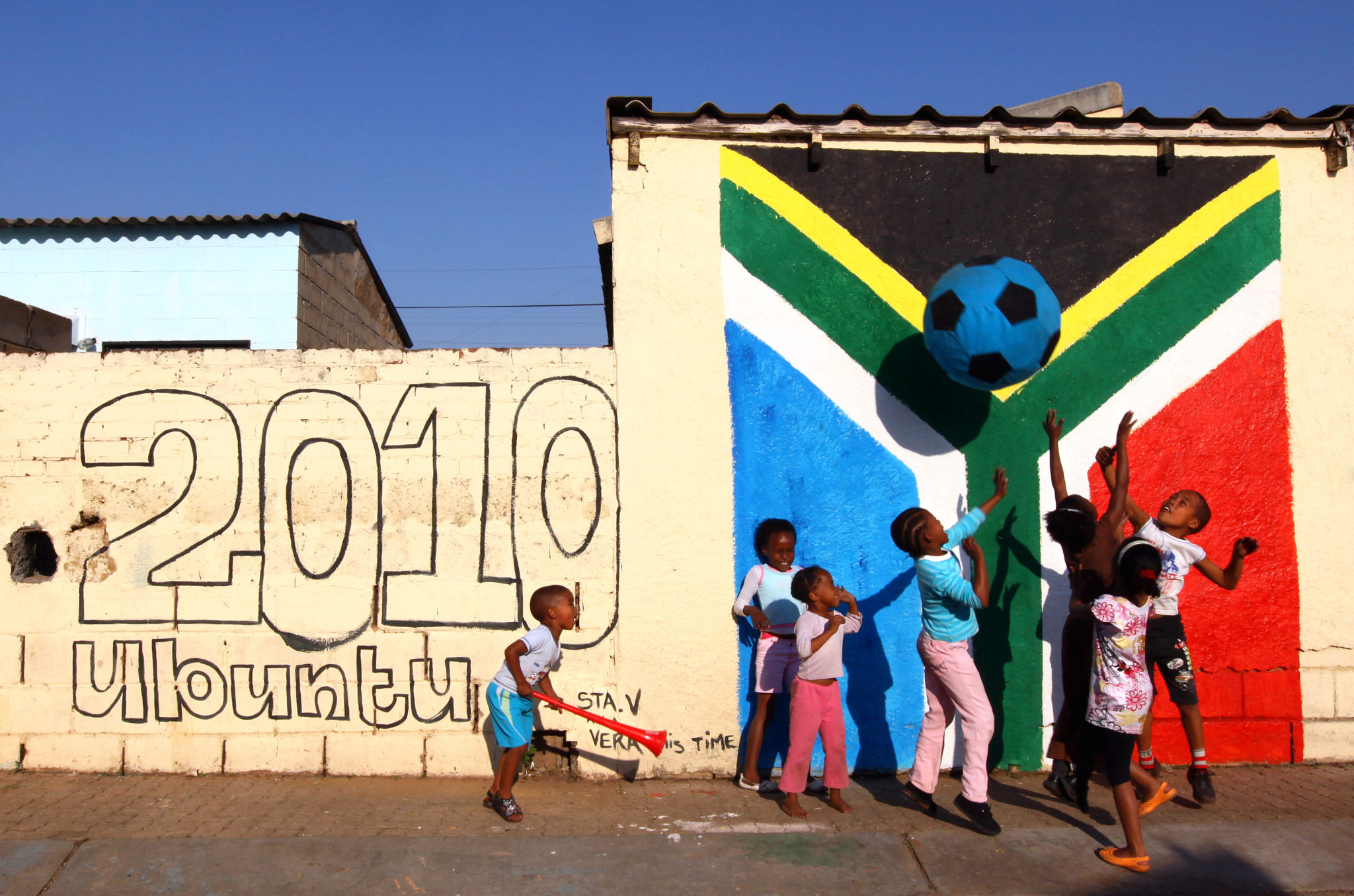 24 May 2010, Children play with a ball in Westbury near Johannesburg. With 17 days to go until the first game of the 2010 World Cup soccer fever is taking over the country. Picture: Shayne Robinson