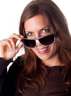 Beautiful smiling brunette looking over her sunglasses over a white background