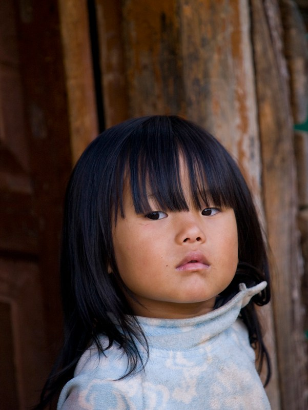 Young Bhutanese girl standing in front of her shed