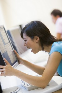 Woman in computer room holding monitor and smiling