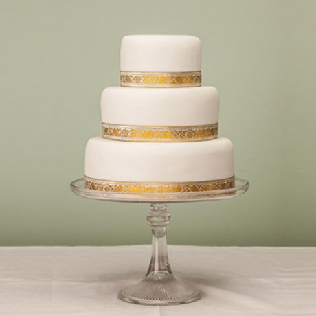 Three tier plain white decorated cake on glass stand