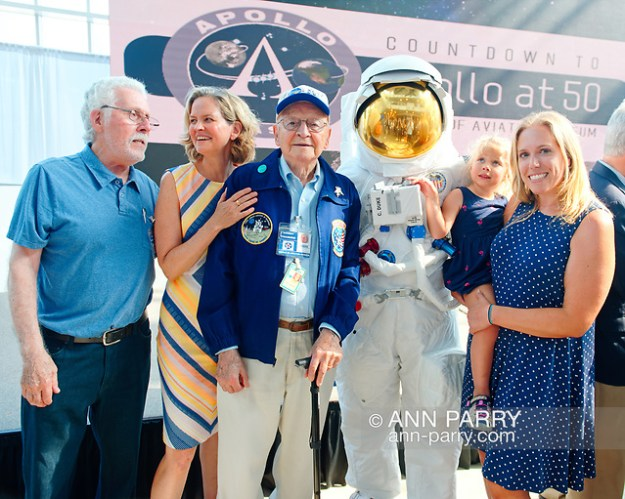 Garden City, New York, U.S. July 20, 2019. L-R, ALAN CONTESSA, Nassau County Executive LAURA CURRAN, ERNEST FINAMORE, TOM RUHLE (wearing space suit), and visitor SUE MOLLER holding child looking up at astronaut helmet, are at Moon Fest Apollo at 50 Countdown Celebration at Cradle of Aviation Museum in Long Island. Contessa and Finamore worked for Grumman on Apollo 11 mission. (© 2019 Ann Parry/Ann-Parry.com)