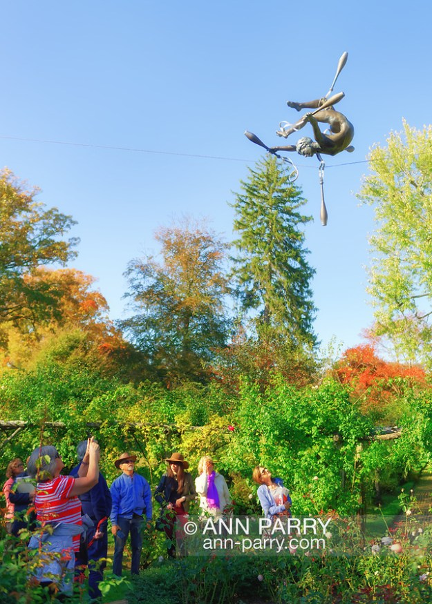 Old Westbury, New York, U.S. October 19, 2019. Tour, led by (at right) Docent LUCY JAFFE and including (at center, wearing brown hat) visitor ROXANNE BINASO, looks up at Juggler with Cudgels, one of Jerzy Kędziora (Jotka) Balance in Nature outdoor sculptures, during Closing Reception for the exhibit, held at Old Westbury Gardens. (© 2019 Ann Parry/Ann-Parry.com)