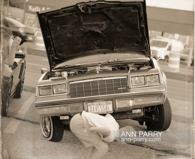 """""""Bellmore, NY, U.S. July 30, 2021. A blue 1984 Buick Regal has eye-catching driver's side front wheel in air and a passenger side front flat tire, and the license plate DAVESSAL, at the Bellmore Friday Night Car Show. (© 2021 Ann Parry/AnnParry.com)"""