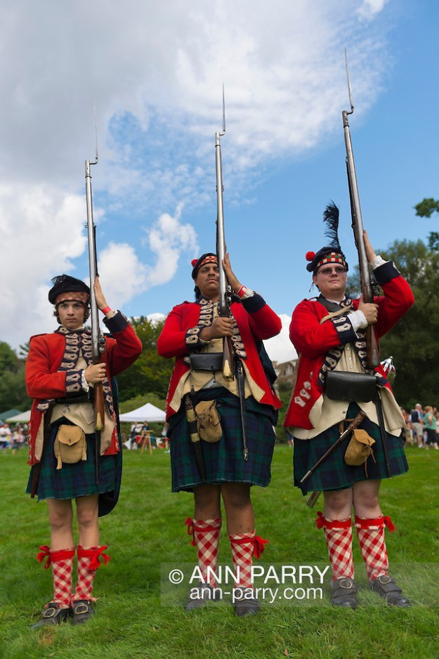 Old Westbury, New York, U.S. - August 23, 2014 - L-R, TIM NORTON, of CT, AARON BOATRIGHT, of CT, and CONRAD BENDER IV, of NJ, are American Revolution re-enactors portraying members of the 42nd Royal Regiment of Foote, at the 54th Annual Long Island Scottish Festival and Highland Games, co-hosted by L. I. Scottish Clan MacDuff, at Old Westbury Gardens. The regiment, The Black Watch, was raised in the Scottish Highlands in 1740 and fought for the British. (Ann Parry/Ann Parry, ann-parry.com)
