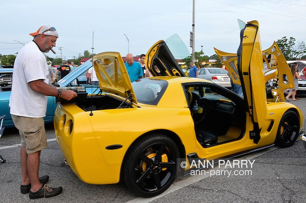 Bellmore, New York, USA. 12th June 2015. Owner Grey Cherveny, of Bay Shore, is standing at the open trunk of his modified yellow 2003 Corvette 50th Anniversary model, with Lamborghini doors (AKA vertical scissors doors and Lambo doors) and chrome trim added, an award winning car displayed at the Friday Night Car Show held at the Bellmore Long Island Railroad Station Parking Lot. Hundreds of classic, antique, and custom cars were on view at the free weekly show, sponsored by the Chamber of Commerce of the Bellmores. (Ann Parry/Ann Parry, ann-parry.com)