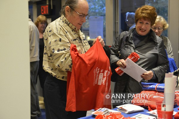 """Oct. 15, 2012 - Hempstead, New York, U.S. - Man attending Simpson and Bowles event at Hofstra puts on red shirt that Fix the Debt Campaign gives free to anyone who puts in on right there in lobby and wears it to event at Hofstra University's John Cranford Adams Playouse., The campaign's co-founders, Simpson and Bowles, speak in the auditorium about ?America's Debt and Deficit Crisis: Issues and Solutions.? This event with the co-chairmen of the National Commission on Fiscal Responsibility and Reform, and co-leaders of Simpson-Bowles non-partisan U.S. fiscal debt reduction plan, was part of """"Debate 2012 Pride Politics and Policy"""" a series of events leading up to when Hofstra hosts the 2nd Presidential Debate between Obama and M. Romney, the next night, October 16, 2012, in a Town Meeting format. (Ann Parry/Ann Parry, ann-parry.com)"""
