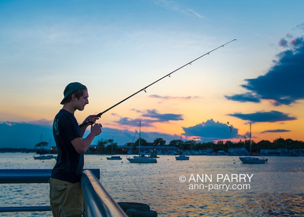 Port Washington, New York, USA. 26th June 2015. A young man, wearing cap backwards, is fishing as sunset approaches, on the Town Dock on the shores of Manhasset Bay in the North Shore village on Long Island Gold Coast. (Ann Parry/Ann Parry, ann-parry.com)