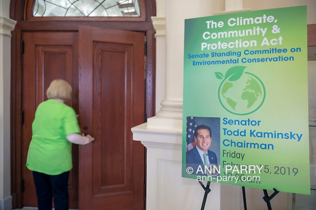 Mineola, NY, USA. 15th Feb, 2019. Activist wearing green Climate Emergency shirt re-enters chamber during NYS Senate Public Hearing on Climate, Community & Protection Act, Bill S7253, Sign next to entrance give info about the bill sponsored by Sen. Todd Kaminsky.  (© 2019 Ann Parry/Ann-Parry.com)