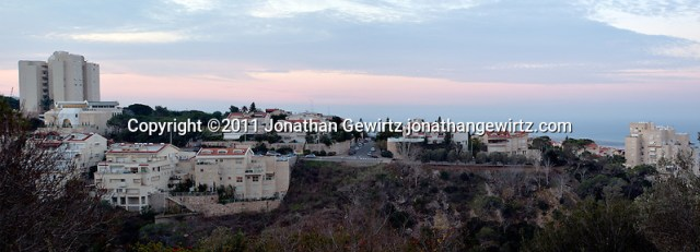Panoramic view of houses and apartment buildings on Haifa's Mount Carmel at dawn with the Mediterranean coast in the background. (Jonathan Gewirtz)