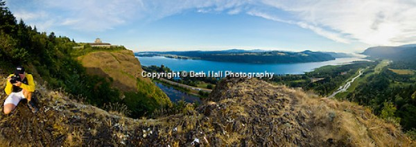 A panoramic image of a photographer taking photos of the Columbia River Gorge from a ridgle that  overlooks the Columbia River and Vista House in Corbett, Oregon. (Beth Hall)