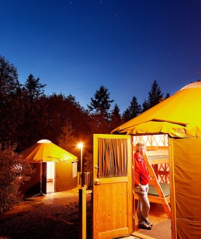 Man standing in open doorway of rental yurts at Kayak Point County Park at dusk, Snohomish County, Washington