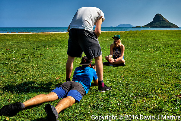 Student being photographed with Mokoli?i (Chinaman's Hat) in the background. Kualoa Regional Park on the north shore of Oahu. Image taken with a Fuji X-T1 camera and 23 mm f/1.4 lens (ISO 200, 23 mm, f/16, 1/250 sec). (David J Mathre)