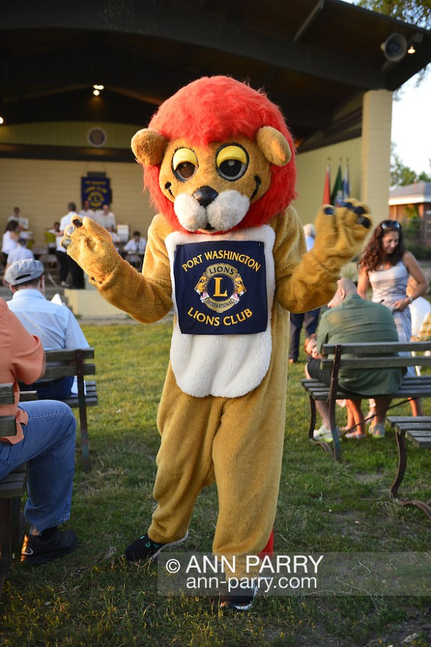 Port Washington, New York, U.S. July 11, 2014. Wearing a Lions Club mascot costume, a Port Washington Lions Club member greets visitors before the outdoor band concert at John Philips Sousa Memorial Band Shell, in Sunset Park in n the North Shore village on Long Island Gold Coast. (© 2014 Ann Parry/Ann-Parry.com)