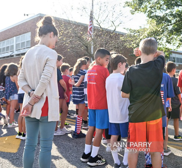 North Merrick, New York, U.S. September 11, 2019. At Park Avenue School students and staff listen to a patriotic song, and then each class with its teacher paused in front of the 9/11 Memorial Garden garden in front of the entrance, on their way back into the school. Earlier in ceremony, Principal E. Speidel of the K-6 elementary school talked about the significance of 911 and the 9/11 Memorial Garden, on the 18th Anniversary of the terrorist attacks Sept. 11, 2001. (Ann Parry/Ann Parry, ann-parry.com)