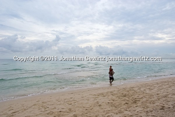An adult carries a child through the surf on Miami Beach. (Jonathan Gewirtz)