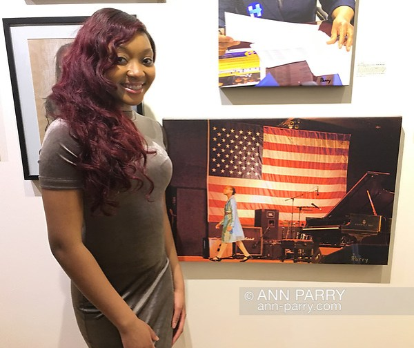 "Huntington, New York, USA. March 5, 2017. Sheimyrah Mighty, 18, next to 2008 photo of herself, at Opening Reception for ""Her Story Through Art"" Invitational Art Show, celebrating Women's History Month, at Huntington Arts Council, Main Street Gallery. Artists Tara Leale Porter, Irene Vitale, Anahi DeCanio, Ann Parry, Show March 2 - 25, 2017. (Ann Parry/Ann Parry, ann-parry.com)"