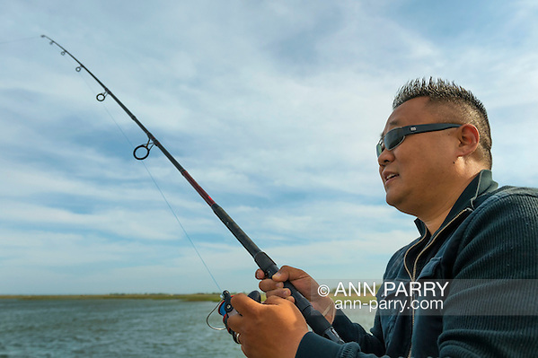 Merrick, New York, USA. May 24, 2015. Rev. DAVID YI, of Douglaston, Queens, fishes on the pier of Levy Park & Preserve during Memorial Day Weekend. (© 2015 Ann Parry/Ann-Parry.com)