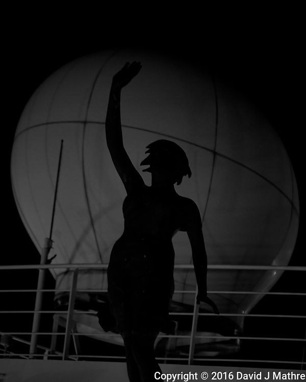 Early morning silhouette of the forward statue against the satellite communication dome from the forward upper deck of the MV World Odyssey. Image taken with a Fuji X-T1 camera and 35 mm f/1.4 lens (ISO 1600, 35 mm, f/1.4, 1/30 sec). (David J Mathre)