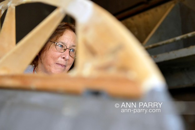 """""""Garden City, New York, USA. July 8, 2012. Volunteer KATHLEEN WOJCIESZAK helps recreate wing of historic aircraft for Danish government at Cradle of Aviation air hanger (© 2012 Ann Parry/AnnParry.com)"""