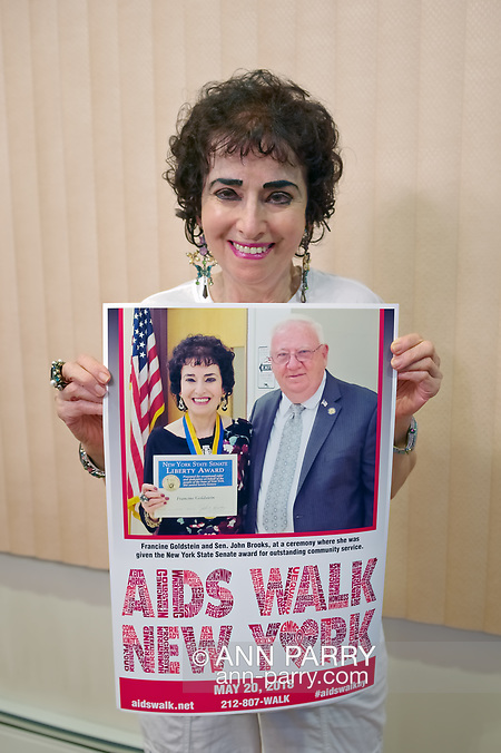 Merrick, New York, USA. May 3, 2018. FRANCINE GOLDSTEIN holds special poster AIDS WALK NEW YORK created for her. At top of poster is photo of Sen. JOHN E. BROOKS presenting her with NYS Senate Liberty Award. (© 2018 Ann Parry/Ann-Parry.com)