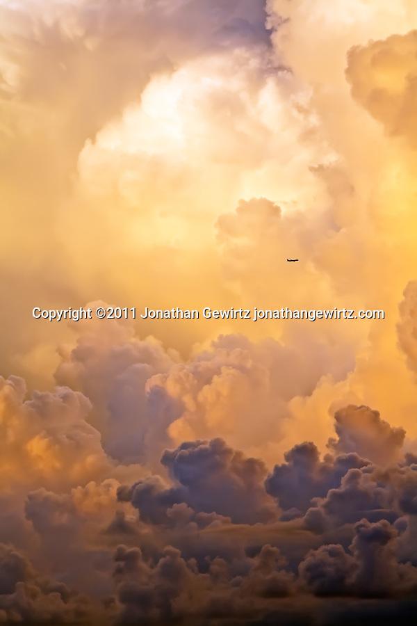 A distant airplane flies past towering thunderstorm clouds. (Copyright 2011 Jonathan Gewirtz jonathan@gewirtz.net, Jonathan Gewirtz jonathan@gewirtz.net)