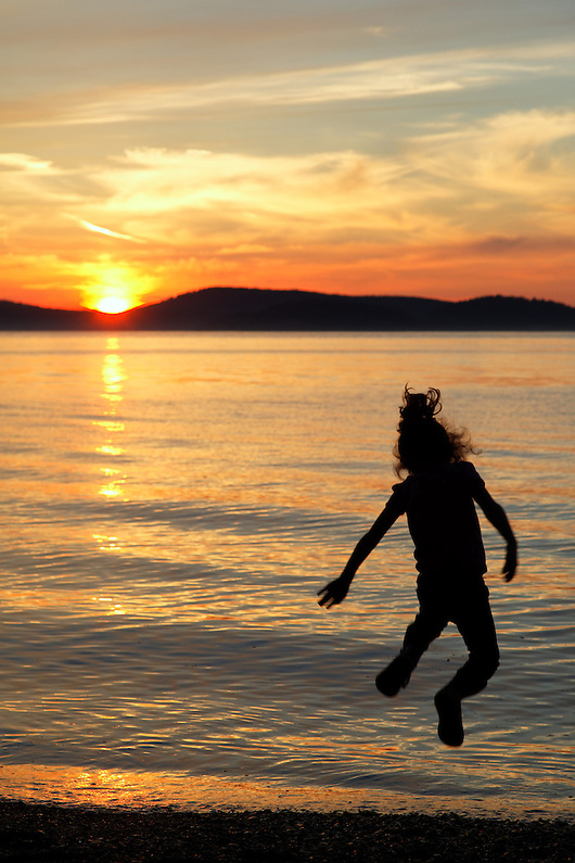 Girl leaping into the air above the setting sun, Sunset Beach, Washington Park, Anacortes, Skagit County, Washington (Brad Mitchell)