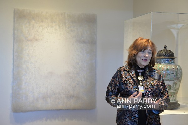 Roslyn, New York, USA. January 2, 2015. LINDA SCHWARTZ, a docent shares information about the artwork exhibits at the Nassau County Museum of Art China Now and Then Exhibit on Long Island. Artwork on wall by Chinese artist Lin Tianmiao is Digital Photograph on canvas with thread, with eyes nose and lips of face faintly visible. (Ann Parry/Ann Parry, ann-parry.com)