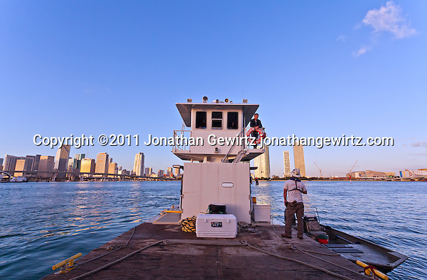 The Peggy Ann, a utility barge in Miami harbor with the Miami bayfront in the background. (© Jonathan Gewirtz)