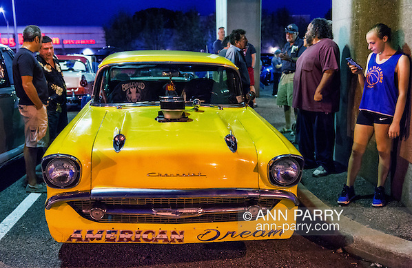 Bellmore, New York, USA. 7th August 2015. Groups of people are at 1957 Chevrolet muscle car, with a blower (supercharger air compressor) sticking out through hole in hood, and American Dream written under the front grill, and parked under the elevated train tracks at the Friday Night Car Show held at the Bellmore Long Island Railroad Station Parking Lot. (Ann Parry/Ann Parry, ann-parry.com)