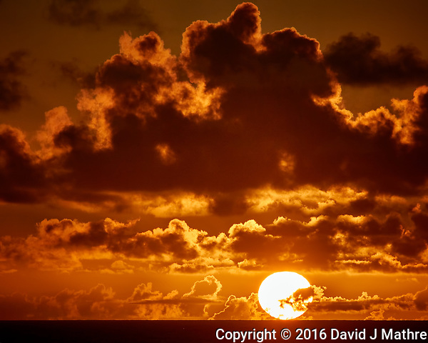 Sun rising through the orange clouds viewed from the aft deck of the MV World Odyssey. Image taken with a Nikon 1 V3 camera and 70-300 mm VR lens (ISO 200, 144 mm, f/8, 1/2000 sec). Raw image processed with Capture One Pro, noise reduction with Topaz DeNoise 5 (David J Mathre)