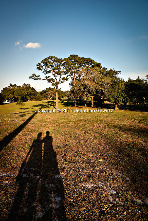 Late-afternoon shadows of two people standing next to each other in a grassy field with trees and sky in the background. (Jonathan Gewirtz)