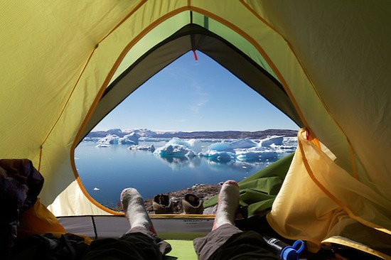 Camper's feet and view out door of tent onto icebergs on Sermilik Fjord near settlement of Tiniteqilaq, East Greenland (Brad Mitchell)