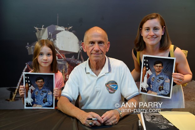 Garden City, New York, U.S. July 20, 2019. At center, NASA Space Shuttle astronaut BOB CENKER poses with, at left, LUCY DEEGAN, 8, and MEREDITH DEEGAN, both of Swords, a town near Dublin, Ireland, at the Moon Fest Apollo at 50 Countdown Celebration at Cradle of Aviation Museum in Long Island. (© 2019 Ann Parry/Ann-Parry.com)