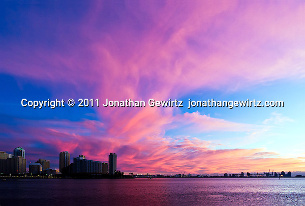 The warm light of the rising sun dramatically tints clouds over the Port of Miami, Florida. (© Jonathan Gewirtz, jonathan@gewirtz.net)
