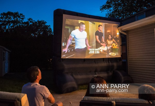 "Merrick, New York, USA. 11th June 2017. At bottom left, CHRIS EDOM, ""American Grit"" TV contestant, 48, of Merrick, hosts backyard Viewing Party for Season 2 premiere. The Fox network reality television series show projected on large screen, with (L-R) JOHN CENA, and 2 of his Cadre members, JOHN BURKE and RIKI LONG. Edom was last contestant picked for a team that episode. (Ann Parry/Ann Parry, ann-parry.com)"