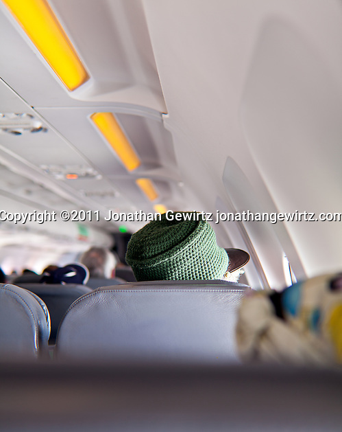 Rastafarian hat wearer sitting a few rows ahead of the camera on a plane. (Jonathan Gewirtz)