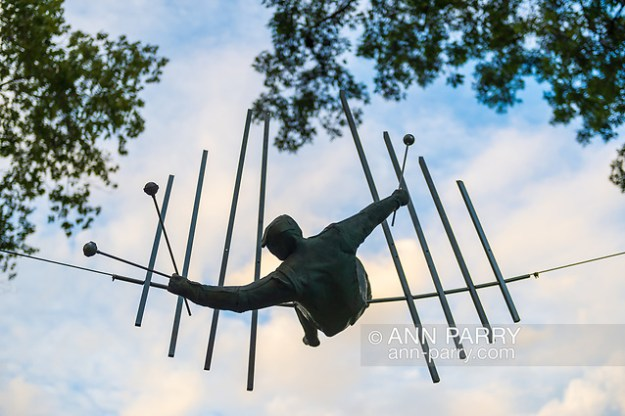 "Old Westbury, New York, U.S., September 1, 2019. ""The Last Show False Tone"" is one of 33 outdoor sculptures by Jerzy Kędziora (Jotka), b. 1947 in Poland, and his Balance in Nature art is on view at historic Old Westbury Gardens in Long Island, until October 20, 2019. Seen almost silhouetted by the sky, the life-size, bronze resin balancing sculpture, high on a wire suspended between trees, is of a musician holding three mallets to hit notes on 8 bars. (© 2019 Ann Parry/Ann-Parry.com)"