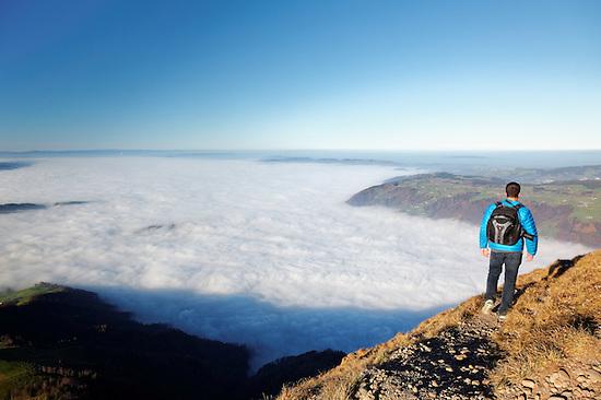 Man hiking above foggy valley from near summit of Mount Rigi, Bänderenweg route, Switzerland, Europe (Brad Mitchell)