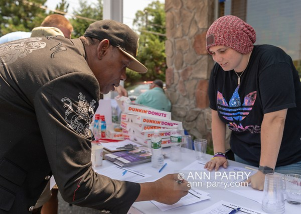 Massapequa, NY, USA. August 5, 2018. Supporter writes in Volunteer Sign-In sheet, during joint campaign office opening for Liuba Grechen Shirley, Congressional candidate for NY 2nd District, and NY Sen. John Brooks. (© 2018 Ann Parry/Ann-Parry.com)