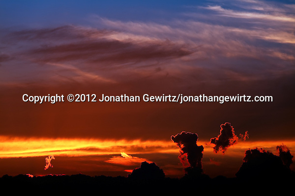 Billowing layers of distant clouds are dramatically backlit by warm orange light from the setting sun. (©2012 Jonathan Gewirtz/jonathangewirtz.com)